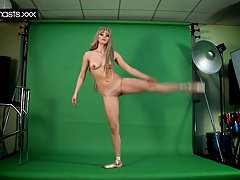 Гибкая блондинка балерина делает растяжку перед камерой, в то время ка...