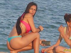 Красивые девушки отлично проводят время на пляже, а парни смотрят на н...
