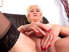 Бабушка блондинка с красными ногтями одета в черные чулки, делая соло